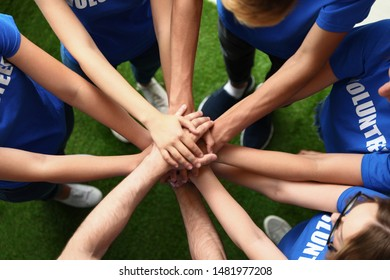 Group of volunteers joining hands together outdoors, top view