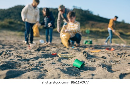 Group of volunteers picking up trash on the beach. Selective focus on plastic lid in foreground