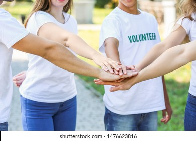 Group of volunteers putting hands together outdoors