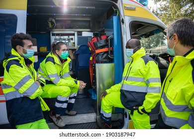 Group of volunteers taking a break from service near the ambulance waiting a call - People working in first aid with uniform wearing face mask for protection infection Coronavirus, Covid-19