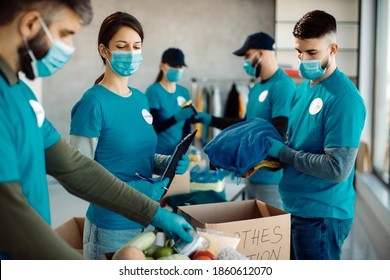 Group of volunteers wearing protective face masks while packing food and clothes in donation boxes.