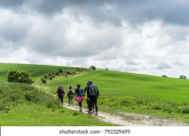 Group walking the South Downs Way, Sussex. A winding path passes fresh green fields on a stormy, overcast, Spring day.