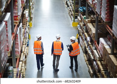 Group of warehouse workers wearing hardhats and reflective jackets waking in aisle between tall racks with packed goods, back view