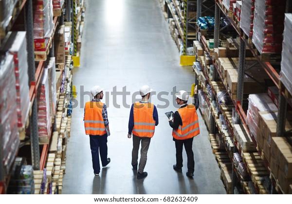 Groupe d'ouvriers d'entrepôts portant des chapeaux durs et des vestes réfléchissantes se réveillant dans l'allée entre de grands racks et des marchandises emballées, vue arrière