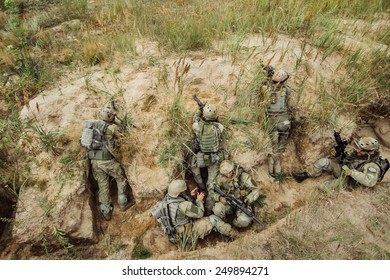 group of warriors hiding in the trenches and firing