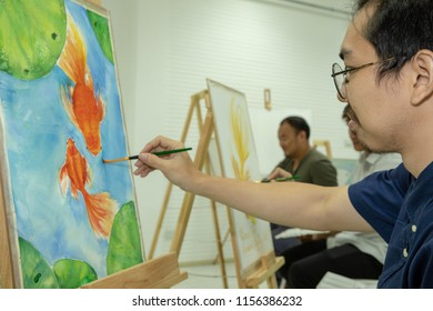A group of water colour artist is painting their pictures in a studio.