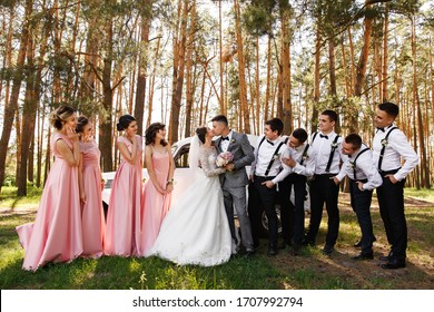 Group wedding photo. Bride and groom kisses near friends, bridesmaids in pink dresses and groomsmen with bow ties and suspender looks at newlyweds