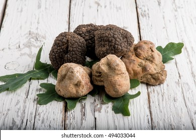 group of white and black truffle over wood background