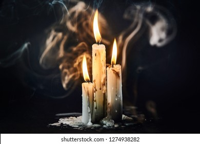 A group of white candles burning in the dark in smoke with dripping wax