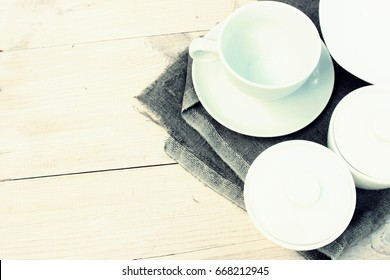 Group of white crockery. Cup, bowls, dish on wooden table with rough grey linen napkin. Homeware theme. Copy space
