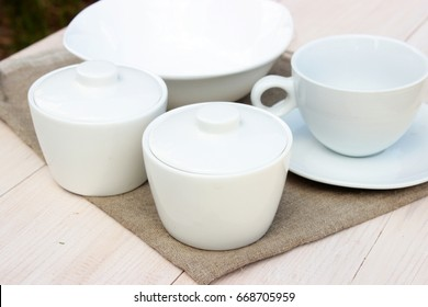 Group of white crockery. Cup, bowls, dish on wooden table with rough grey linen napkin. Homeware theme