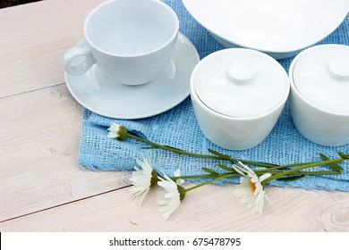 Group of white crockery. Cup, bowls, dish on wooden table with blue linen napkin and a few flowers of daisy. Homeware theme