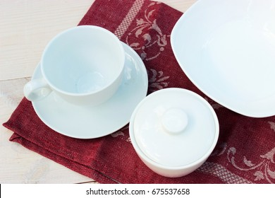 Group of white crockery. Cup, bowls, dish on wooden table with red linen napkin. Homeware theme