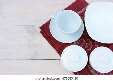 Group of white crockery. Cup, bowls, dish on wooden table with red linen napkin. Homeware theme. Copy space