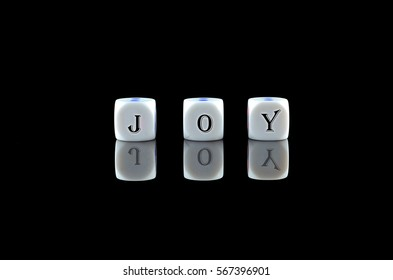 Group of White dice over black background with word written JOY