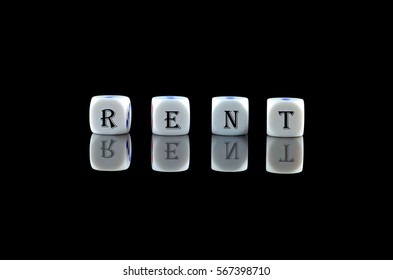 Group of White dice over black background with word written RENT