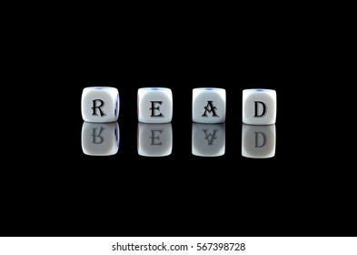 Group of White dice over black background with word written READ