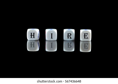 Group of White dice over black background with word written HIRE