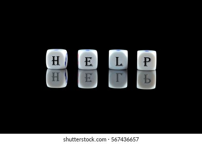 Group of White dice over black background with word written HELP