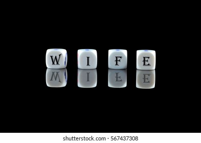 Group of White dice over black background with word written WIFE