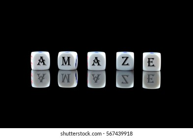 Group of White dice over black background with word written AMAZE