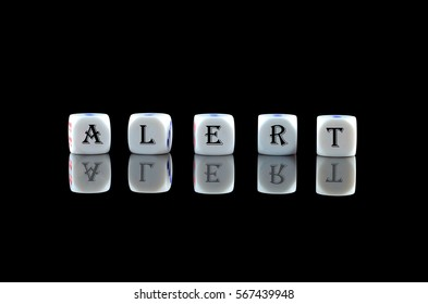 Group of White dice over black background with word written ALERT