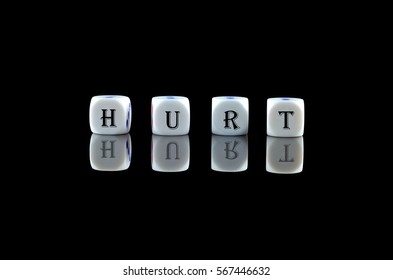 Group of White dice over black background with word written HURT