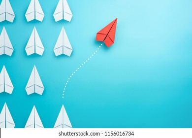 Group of white paper plane in one direction and one red paper plane pointing in different way on blue background. Business for innovative solution concept.