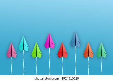 Group of white paper plane in one direction and one red paper plane pointing in different way on blue background.