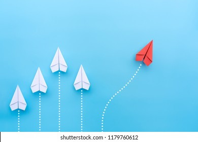 Group of white paper planes in one direction and one red paper plane pointing in different way on blue background. Business for new ideas creativity and innovative solution concepts.