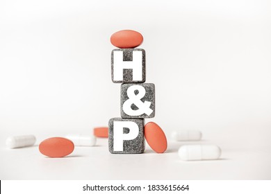 a group of white and red pills and cubes with the word HP History and physical examination on them, white background. Concept carehealth, treatment, therapy.
