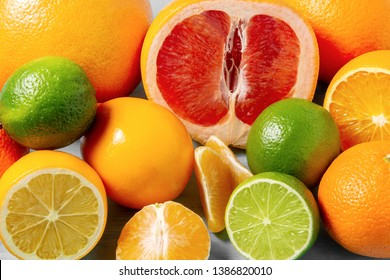group of whole and sliced citrus fruits - tangerines, lemons, limes, oranges, grapefruits on the surface of the table - image