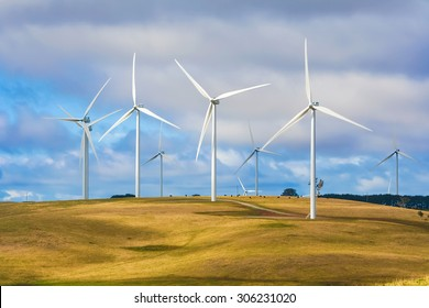 Group of wind turbines at a wind farm on a hill with cattle grazing beneath, creating renewable energy in Taralga NSW Australia.