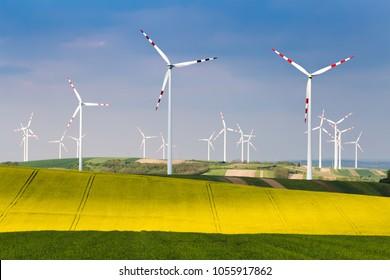 Group of wind turbines on blue sky background. Alternative energy system background.