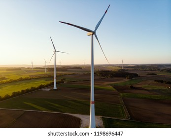 Group of Windmills in aerial drone view in sunset.