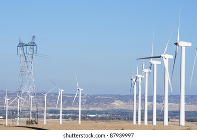group of  windmills for electric power  production and high voltage tower