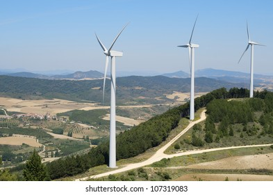 group of windmills for renewable electric energy production and pine forest, Aras, Navarre, Spain