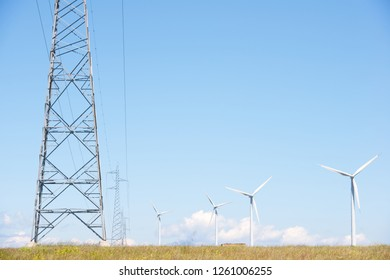 Group of windmills for renewable electric energy production and pylon, Huesca province in Spain.