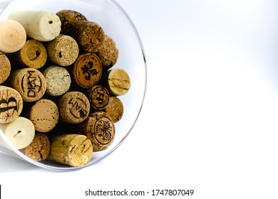 Group of wine corks presented in glass vessel and isolated on white background.