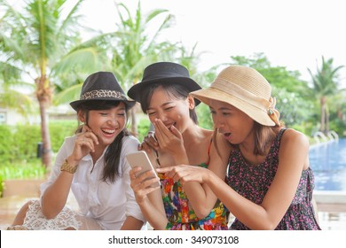 group of woman friend looking to smart phone and laughing with happiness face ,relaxing vacation of people lifestyle