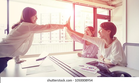 Group of woman giving high five.