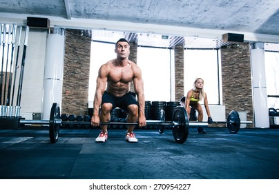 Group of woman and man workout with barbell at gym