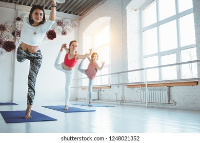 Group of woman practice exercise together indoor class. Healthy lifestyle concept. Females traning together yoga poses in white gym
