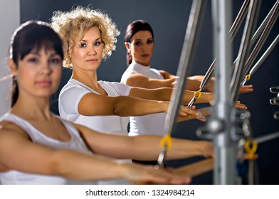 a group of woman is training on a equipment for Pilates exercises in a fitness room