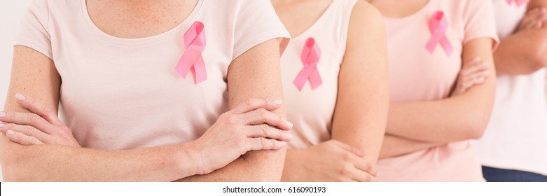 Group of woman wearing pink ribbons as a symbol of fighting breast cancer