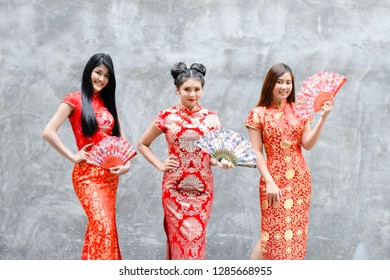 Group of woman wearing red cheongsam dress and holding China blow. The Year of the Pig, Chinese New Year concept.