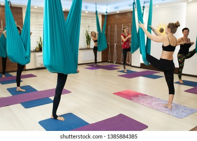 group of womans doing fly yoga stretching exercises in gym. Fit and wellness lifestyle.