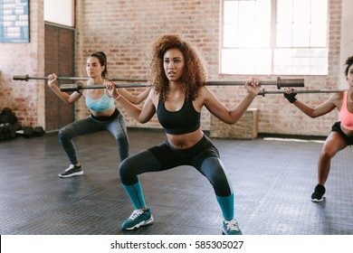 Group of women with barbells in gym. Multiracial group of females exercising together in fitness class.
