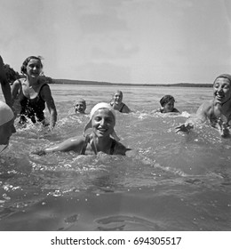 Group of women bathing and swimming in water
