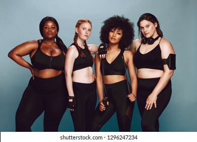 Group of women of different race and body size dressed in sportswear standing together against grey background. Diverse women in sports clothing looking at camera.